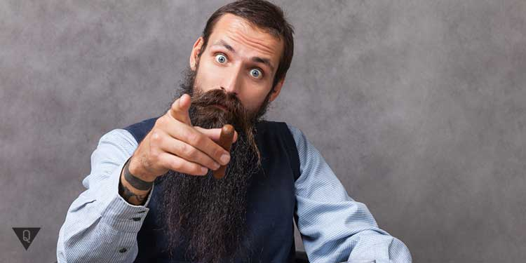 бородатый мужик показывает пальцем