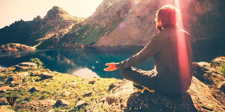 мужчина медитирует в горах