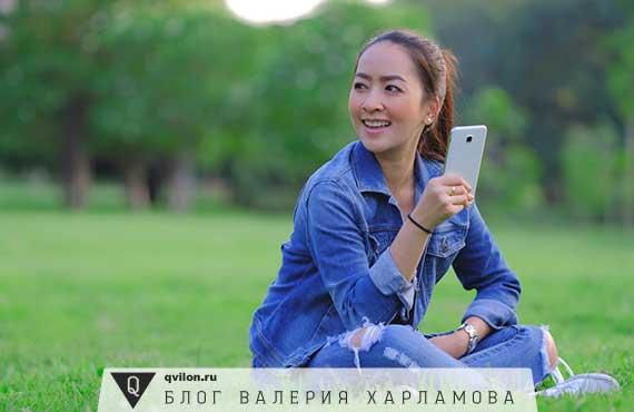 девушка сидит на лугу с телефоном