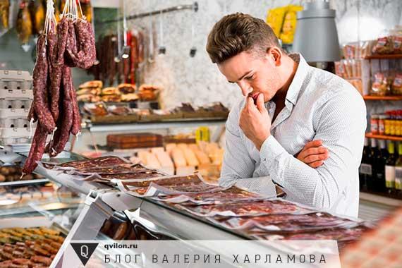 мужчина выбирает колбасу