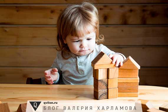 девочка собирает домик из кубиков