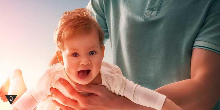 ребенок на руках у папы радуется