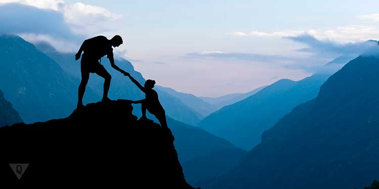 мужчина тянет за руку женщину в горах