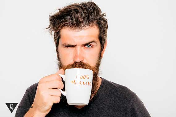бородатый мужик пьёт из стакана с надписью доброе утро