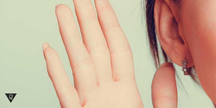 девушка держит руку около уха прислушиваясь