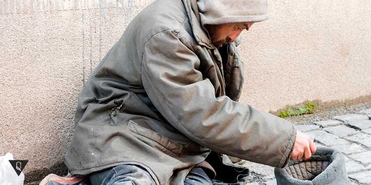 бездомный человек сидит и собирает дань в шапку