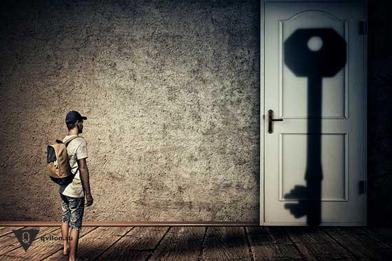 человек стоит перед дверью на которой тень от ключа