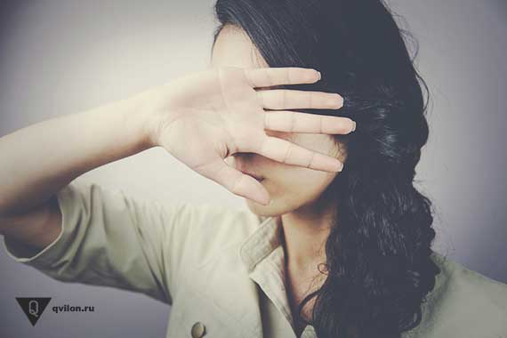 девушка закрывает рукой лицо