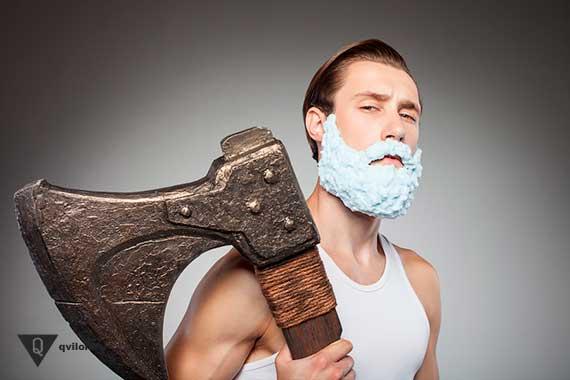 мужчина в пене для бритья держит большой топор