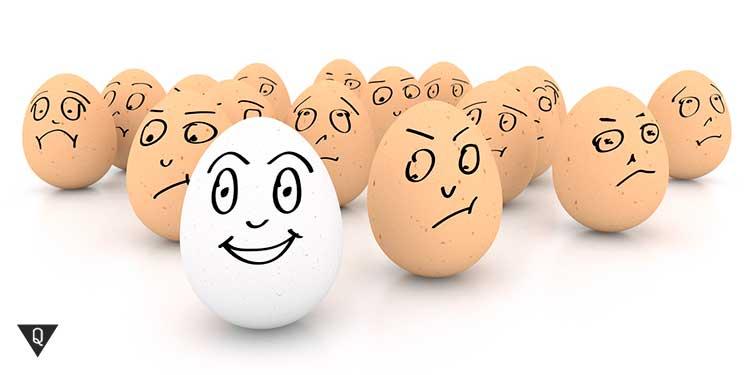 белое яйцо на фоне жёлтых