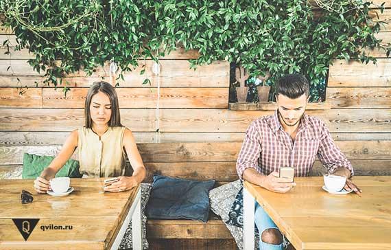 парень и девушка сидят за разными столами