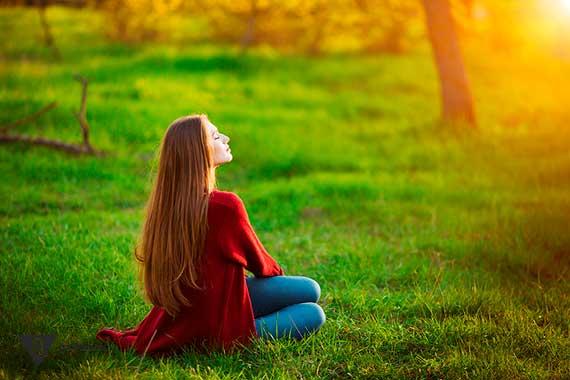 девушка сидит на траве в лесу