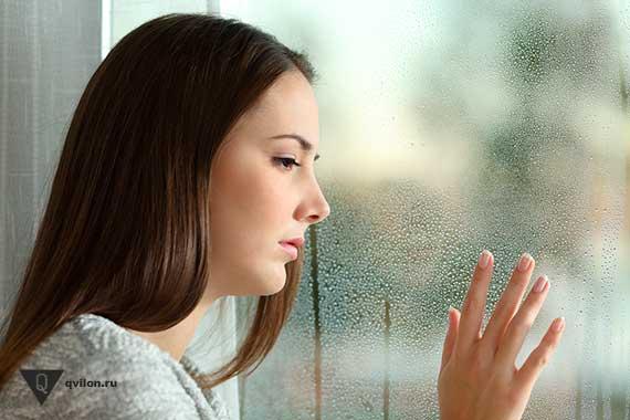печальная девушка стоит у окна