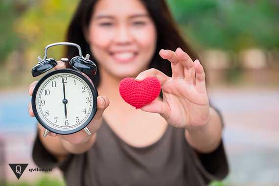 девушка держит часы и вязанное сердце