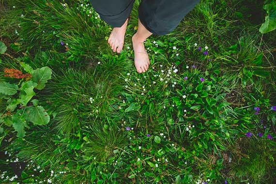 босая женщина стоит на траве