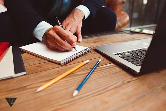 мужчина пишет в блокноте перед компьютером