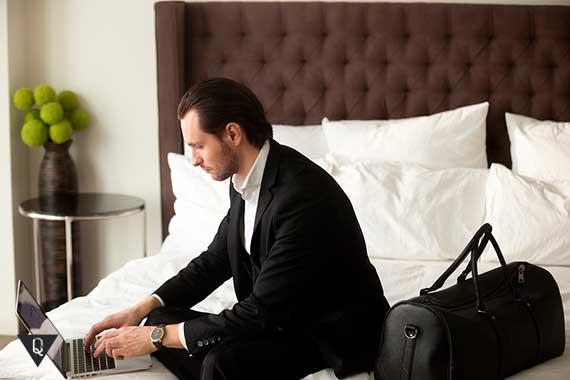мужчина в костюме сидит на кровати за компьютером
