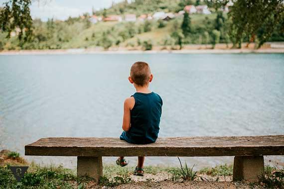 мальчик сидит на лавочке на берегу реки