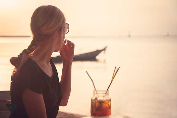 девушка смотрит в море на лодку