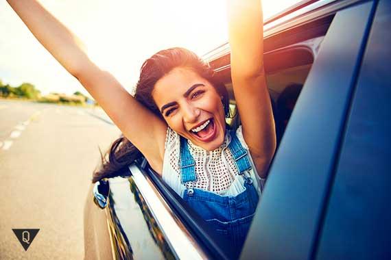 девушка улыбается выглядывая из окна машины