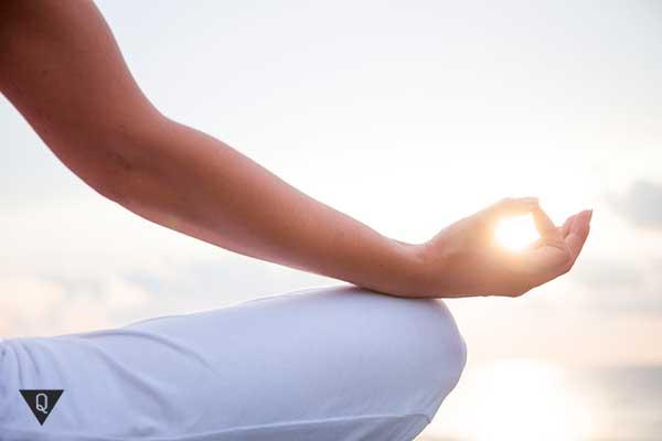 девушка медитирует перед солнцем