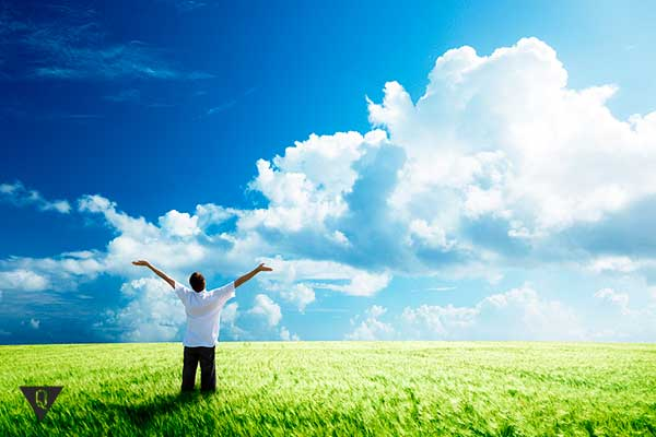 мужчина в поле радуется голубому небу с облаками