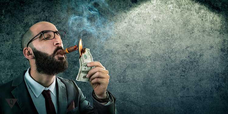 надменный мужчина прикуривает от стодолларовой банкноты