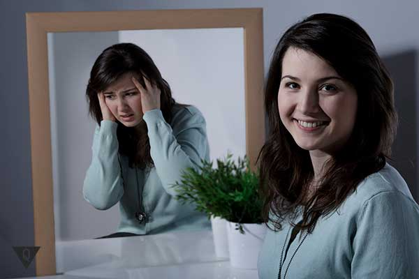 девушка улыбается в то время как её отражение плачет