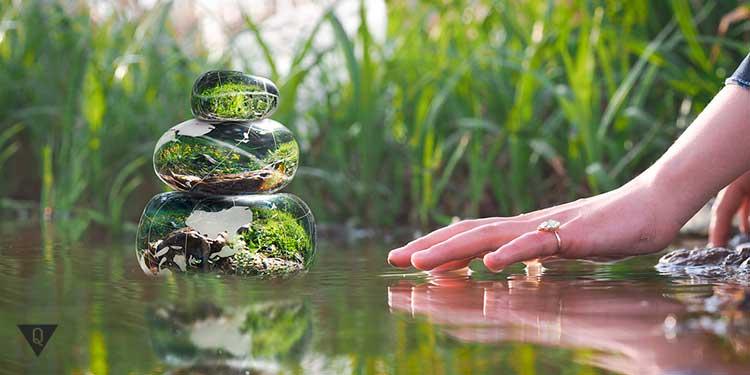 женская рука на фоне зеленой пирамиды дзен