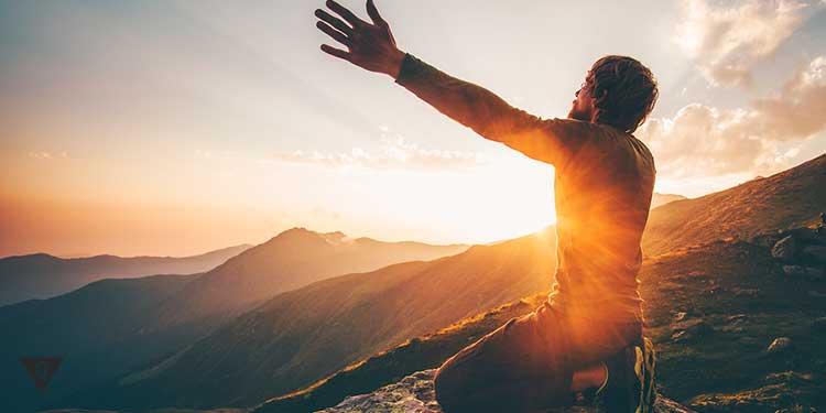 мужчина поднимает руки к закату