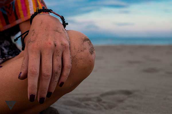 девушка с браслетом сидит на песке