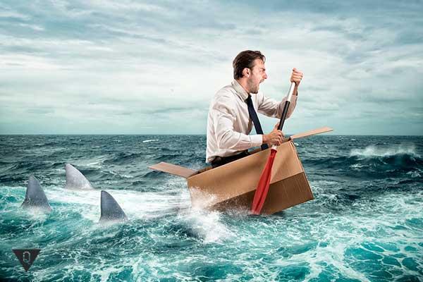 мужчина уплывает в коробке от акул