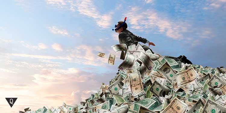 мужчина купается в долларах
