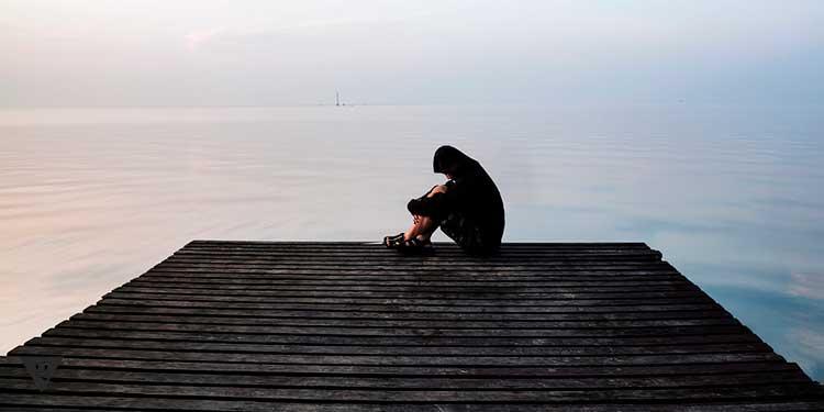 одинокий человек сидит на мостике
