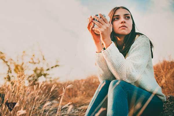 девушка сидит в поле со стаканом в руках