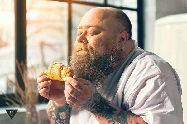 большой бородатый мужчина нюхает круасан