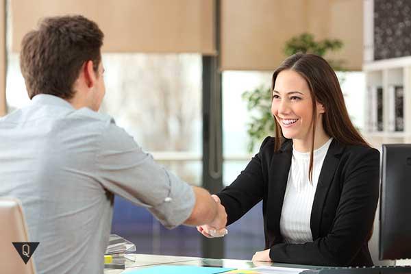 бизнес-вумен радуется пожимая руку мужчине