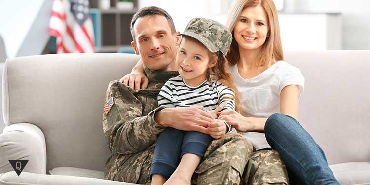 солдат в камуфляже фотографируется с семьёй