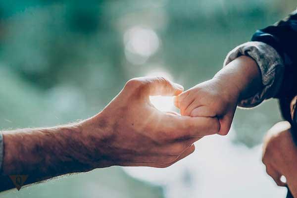 отец держит за руку своего ребенка