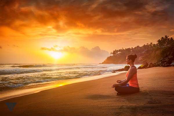 девушка медитирует на пляже на закате