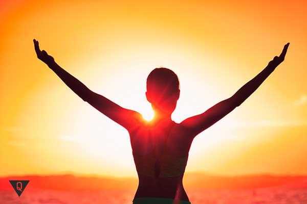 Человек поднимает руки на закате солнца