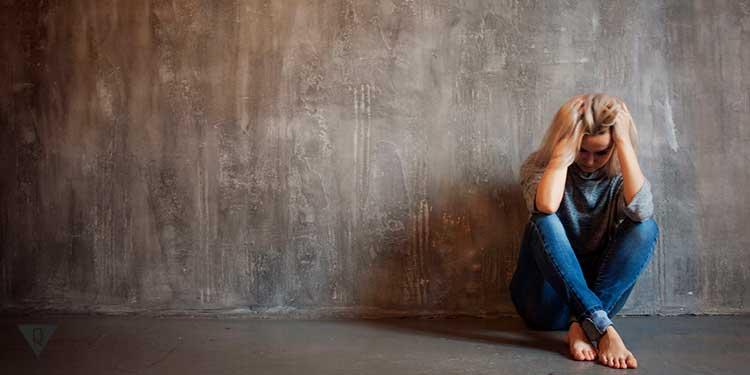 Депрессивная девушка сидит около стены