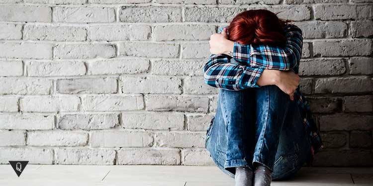 Девушка закрывшись сидит у стены