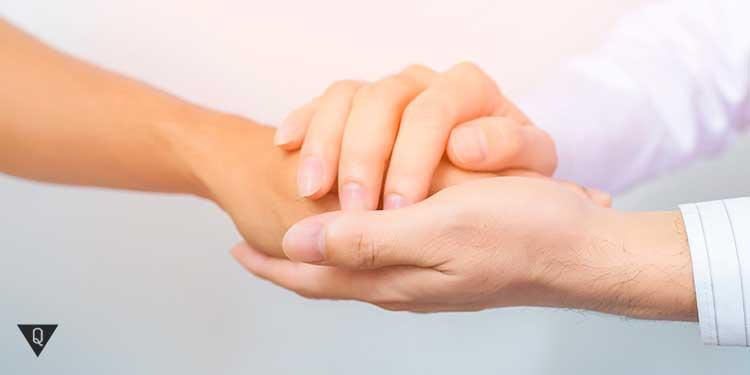 Мужчина нежно держит руку женщины