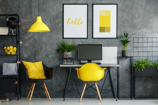 Комната в серых тонах с желтыми стульями и лампой