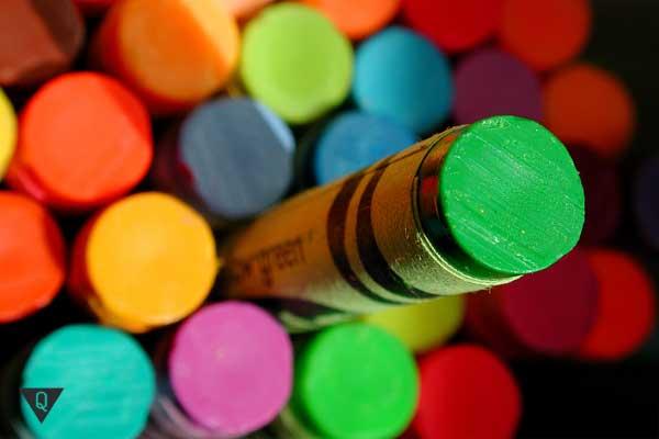 Зеленый карандаш на фоне разноцветных карандашей