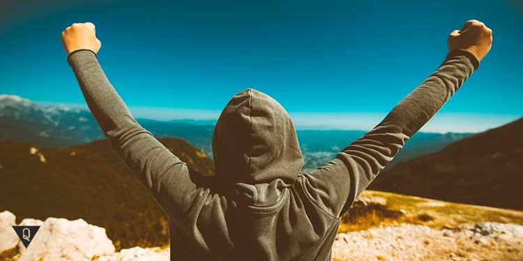 Мужчина держит руки как победитель на фоне гор