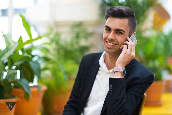 Мужчина говорит по телефону и смотрит в камеру, как символ того, что у него есть чувство собственного достоинства