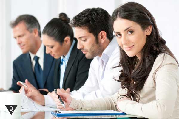 За столом четыре человека, одна женщина уверенно смотрит в камеру, как символ того, что она обладает чувством собственного достоинства