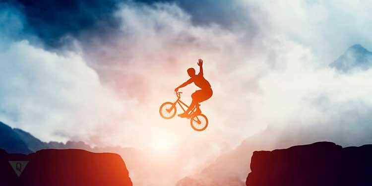 велосипедист летит над пропастью и машет